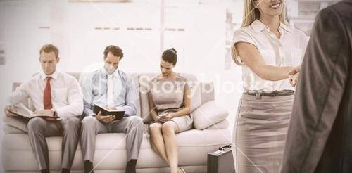 Businessman shaking hands with woman besides people waiting for interview