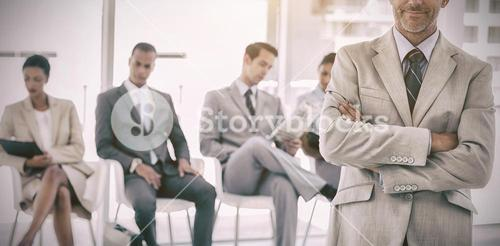 Serious businessman standing in  front of business people
