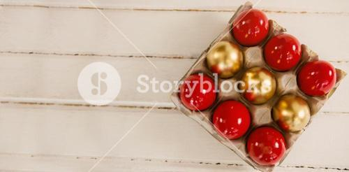 Red and golden Easter eggs in carton