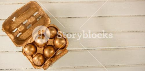 Golden Easter eggs in carton