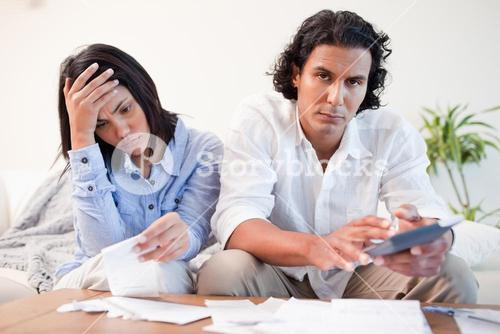 Frustrated couple checking their bills in the living room