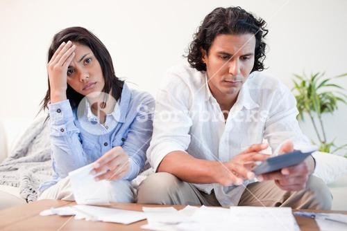 Frustrated couple doing their calculations in the living room
