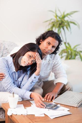 Depressed couple checking their bills