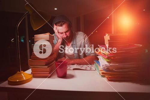 Thoughtful hipster with stacks of books