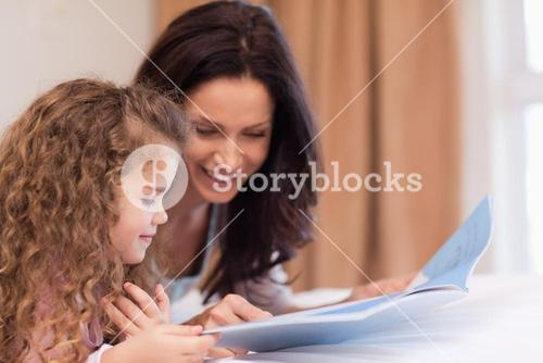Side view of mother and daughter reading a book together