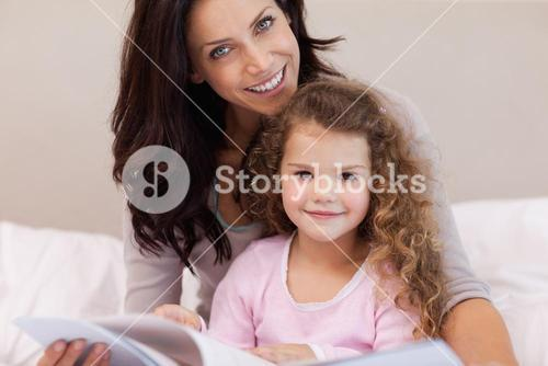 Mother reading a book with her little daughter