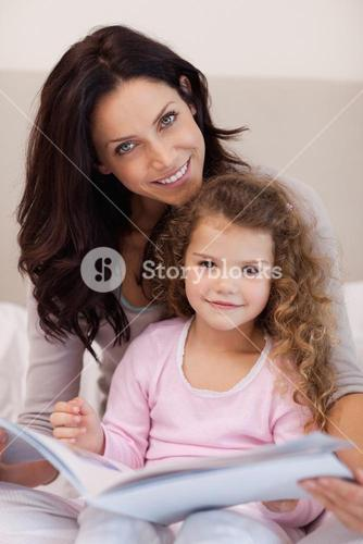 Smiling mother reading a bedtime story with her little daughter