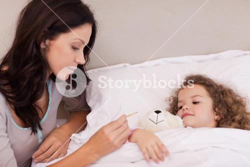 Mother taking her daughters temperature