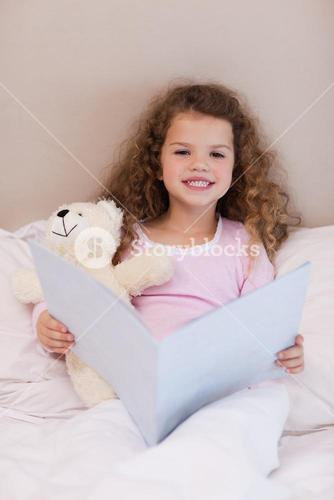 Girl sitting on the bed with a book