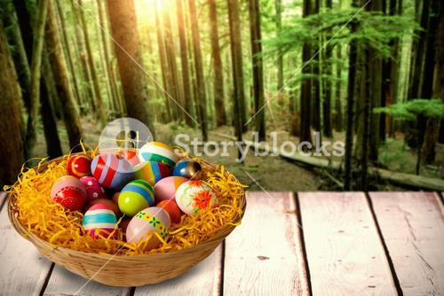 Composite image of multi colored easter eggs in wicker basket