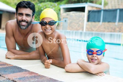 Father and kids smiling in the pool