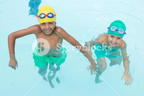 Two smiling kids swimming in the pool