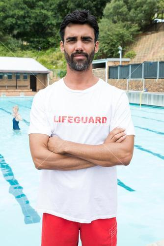 Confident lifeguard standing with arms crossed