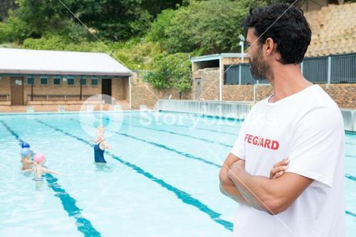 Lifeguard looking at students playing in the pool
