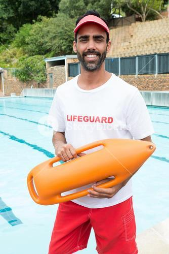 Lifeguard standing with rescue buoy near poolside
