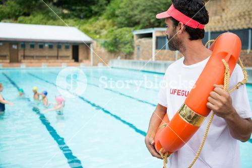 Lifeguard with lifebuoy looking at students playing in the pool