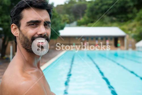 Smiling lifeguard standing near poolside