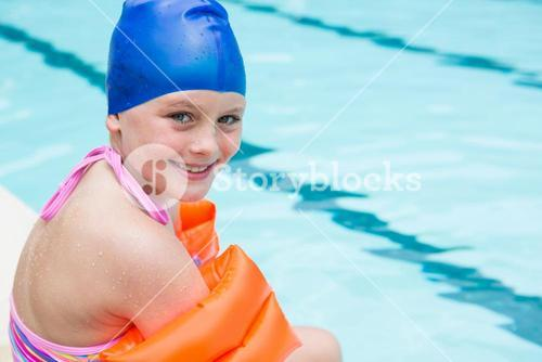 Smiling girl with swim cap sitting near poolside