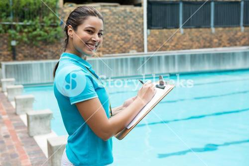 Smiling female coach writing on clipboard