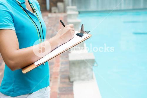 Female coach writing on clipboard near poolside