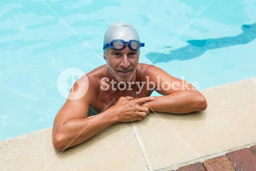 Smiling senior man standing in swimming pool