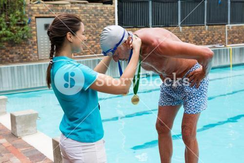 Female coach giving gold medal to senior man