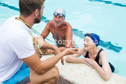 Swim coach showing stop watch to senior couple