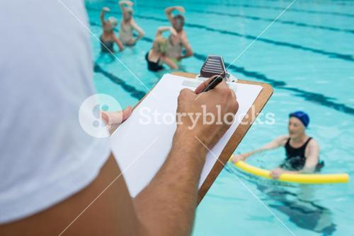 Swim coach writing on clipboard near poolside