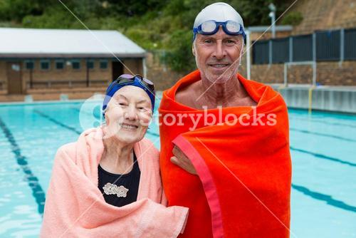 Senior couple wrapped in towel at poolside