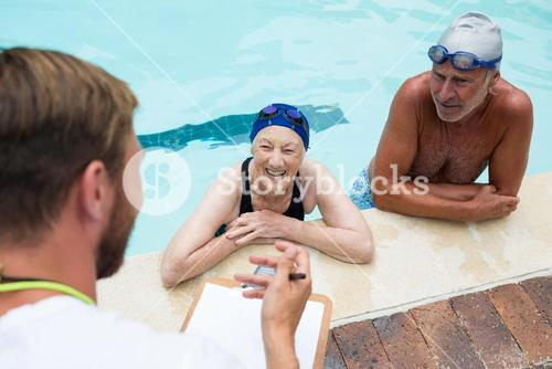 Swim coach interacting with senior couple