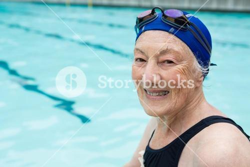 Smiling senior woman sitting at poolside