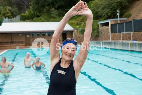 Smiling senior woman excerising at poolside