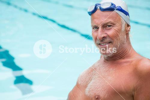 Smiling senior man sitting at poolside