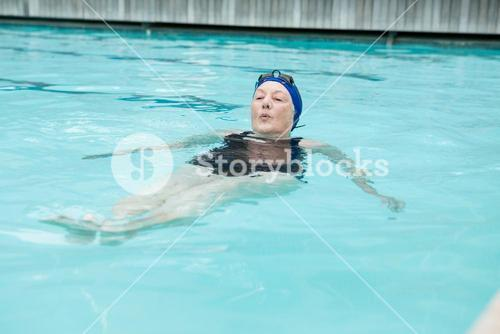 Senior woman swimming in pool