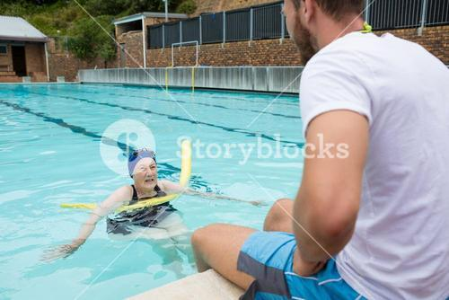 Swim coach interacting with senior woman
