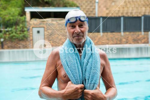 Senior man with towel over his shoulders standing at poolside