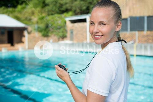Portrait of swim coach holding stopwatch at poolside