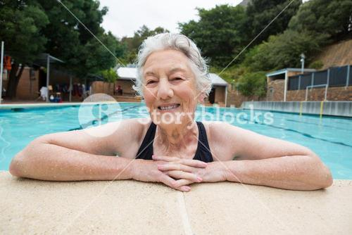 Senior woman leaning on poolside