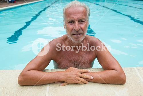 Senior man leaning on poolside