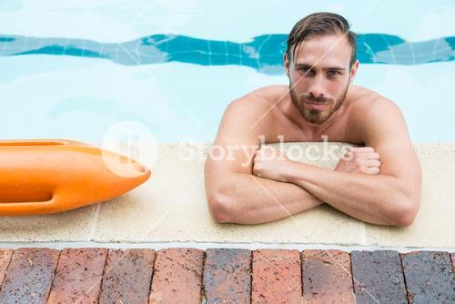 Lifeguard leaning on poolside
