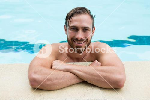 Smiling lifeguard leaning on poolside