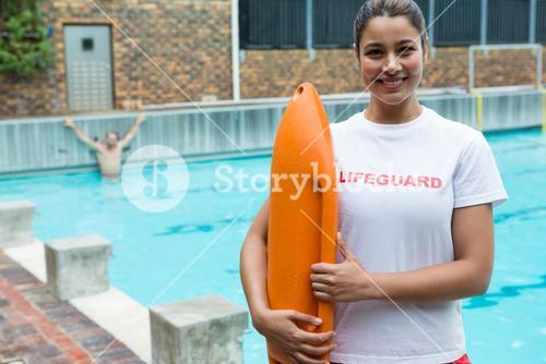 Lifeguard standing with rescue buoy at poolside