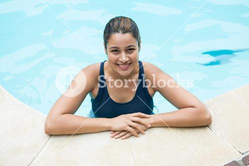 Smiling woman leaning on poolside