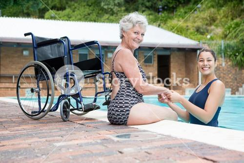 Female coach and senior woman smiling at poolside