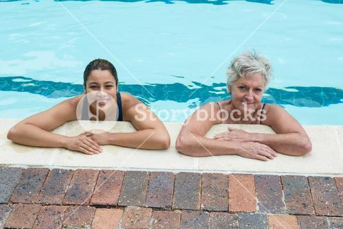 Female coach and senior woman leaning on poolside