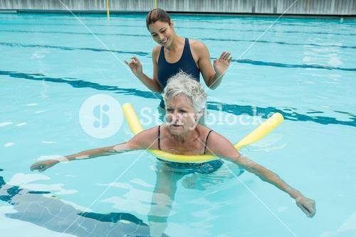 Female coach helping senior woman in swimming pool