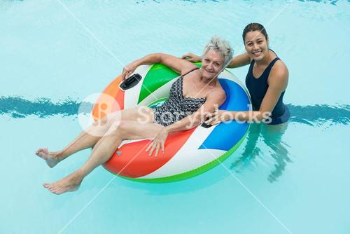 Female coach and senior woman smiling in swimming pool