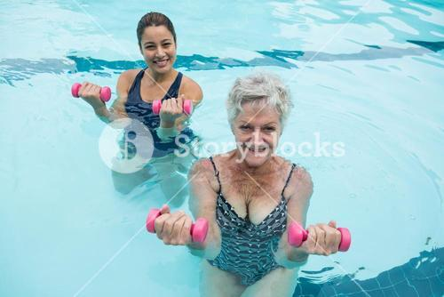 Female coach and senior woman exercising with dumbbells