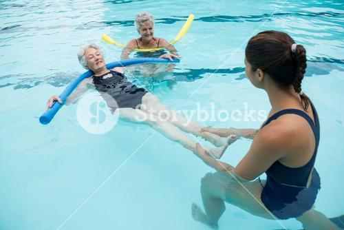 Female coach helping senior women in swimming pool