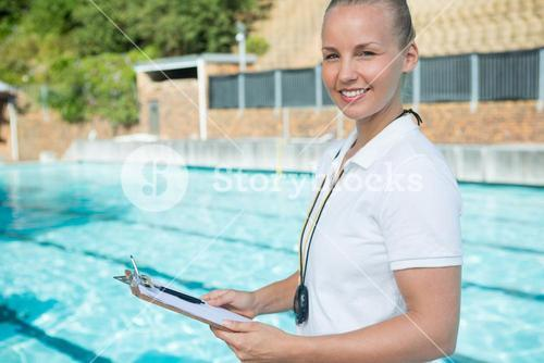 Smiling swim coach holding clipboard at poolside